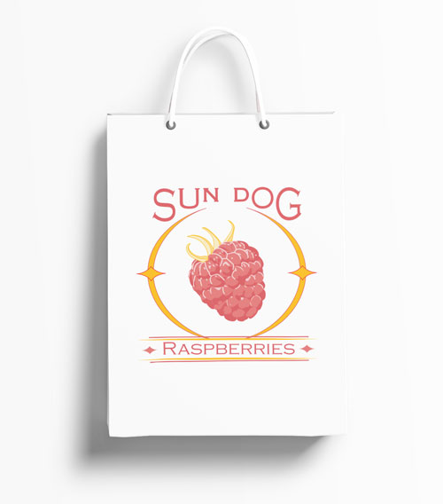 White handled shopping bag with logo for the company Sun Dog Raspberries. Features a raspberry in the center of a circular sun flare known as a sun dog.