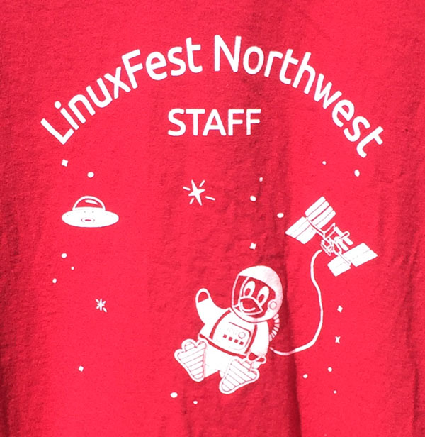 LinuxFest Northwest Staff T-shirt, red, with image of penguin in a space suit connected to the space station with stars and spaceship in the background